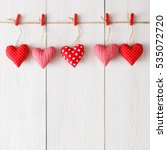 Stock photo valentine background with sewed pillow hearts row border on red clothespins at rustic white wood 535072720