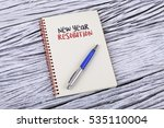 Small photo of New Year Resolution word on a notepad