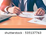 Small photo of Business man working at office with charge sheet and documents on his desk