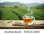 Stock photo tea cup with and tea leaf sacking on the wooden table and the tea plantations background 535211404