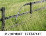 Small photo of Warped top rail of wooden fence in tall grass, for concepts of time, alteration or abnormality