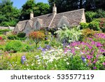 English Country Cottage with beautiful flowers garden in the sunshine in Cotswolds, England, UK