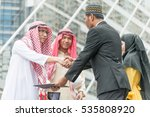 Small photo of Business man from many country shake their hands after agreed an agreement outdoor in front of office building in business area. Business concept