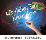 Small photo of Woman Hand Writing Wir Haben Das Know How! (We Have the Know-How in German) with marker over transparent board. Isolated on nature. Business concept. Stock Photo