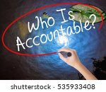 Small photo of Woman Hand Writing Who Is Accountable? with marker over transparent board. Isolated on nature. Business concept. Stock Image
