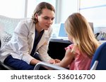 Pediatrician Talking To Unhappy Child In Hospital - stock photo