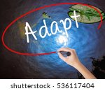 Small photo of Woman Hand Writing Adapt with marker over transparent board. Isolated on nature. Business concept. Stock Photo