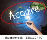 Small photo of Woman Hand Writing Acquire with marker over transparent board. Isolated on nature. Business concept. Stock Photo