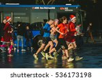 BARCELONA, SPAIN - DECEMBER 25, 2015: Christmas morning, people running with Santa Claus cap - stock photo