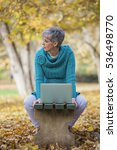 Small photo of Older woman with gray hair in a park with a gray computer sits on a chair in the autumn outdoor ambience