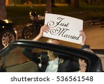 Small photo of A newlywed couple is driving a convertible modern car on a road for their honeymoon. The bride is driving and the husband holding a just married placard, front view
