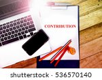 Small photo of CONTRIBUTION word, text at notepad in wooden table background , retro concepts in wooden with notebook and smartphone