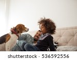 Stock photo cute little girl playing with her dog in the bed 536592556