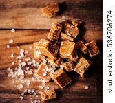 Small photo of Golden Salted caramel pieces and sea salt macro on wooden board
