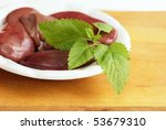 Plate of pork kidneys decorated  with lemon balm - stock photo