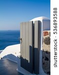 Small photo of Classical Greek gate in the fence. On the background of the sea , the volcano and the Cyclades.
