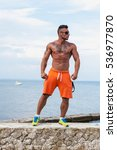 man athlete stands on a rock by ... | Shutterstock . vector #536977870