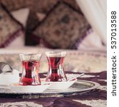 Small photo of Two turkish tea cups and turkish delight with oriental canopy bed at the background. Silver tray. Romantic concept. Valentines background. Arabian nights ambiance. Square, toned