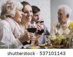 Small photo of Two smiling women sitting at the table and drinking wine during family dinner