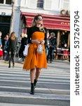 Small photo of PARIS-JANUARY 25, 2016. Helena Bordon is wearing an orange Christian Dior dress on the way to the Christian Dior Fashion show. Haute couture. Paris fashion week.