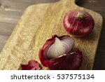 Small photo of Red bisect onion on wooden table. Close-up from above.