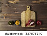 Small photo of Red bisect onion, tomato, yellow spice on wooden table with cutting board.