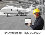Stock photo engineer looking at laptop for maintenance an airplane are performing repairs fixes modernization 537703420