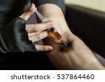 Small photo of Addict hands making syringe injection of heroin.