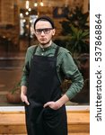 Small photo of Young barman in black apron