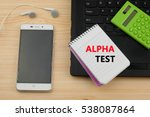 Small photo of ALPHA TEST text written on a notebook. Wooden background with laptop,phone and calculator. Business and management concept.