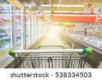 Supermarket aisle with empty green shopping cart        - stock photo