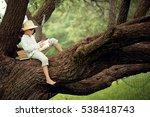 A Boy In A Straw Hat Reading A...