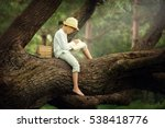 a boy in a straw hat reading a... | Shutterstock . vector #538418776
