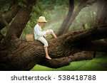 A Boy In A Straw Hat Reading A...