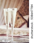 Small photo of Two champagne glasses with oriental canopy bed at the background. Silver tray. Romantic concept. Valentines background. Arabian nights ambiance. Vertical, close up, toned