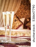 Small photo of Two champagne glasses with oriental canopy bed at the background. Silver tray. Romantic concept. Valentines background. Arabian nights ambiance. Vertical, toned