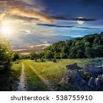 Concept day and night time change. Winter meets spring composite landscape. Valley with trees and boulders on a grass. Road through meadow goes to forest in mountains with snowy peak under cloudy sky - stock photo