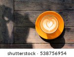 a cup of coffee on the orange... | Shutterstock . vector #538756954