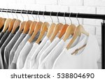 Stock photo black grey and white t shirts on hangers against brick wall close up view 538804690