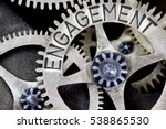 Small photo of Macro photo of tooth wheel mechanism with ENGAGEMENT concept letters
