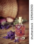 Small photo of Bottle with aroma oil and lavender flowers on wooden background