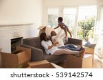 Small photo of Parents Take A Break On Sofa With Son On Moving Day