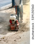 Small photo of Builder worker at sand ground using a vibratory plate compactor to make the sand flat. Man builds road or sidewalk.