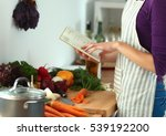 young woman reading cookbook in ... | Shutterstock . vector #539192200