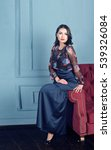 Small photo of the beautiful young woman the brunette in a classical interior, blue plaster, a claret sofa