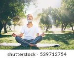 Stock photo yoga at park senior bearded man in lotus pose sitting on green grass concept of calm and 539712754