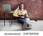Young man playing guitar and composing song in room - stock photo