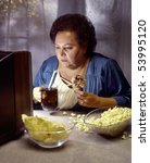 heavy woman watching television while eating - stock photo
