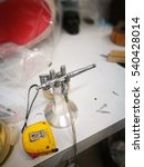 Small photo of airbrush gun on stand with tapes