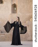 Small photo of young woman in traditional dress (abaya) in Jabrin Castle in Oman